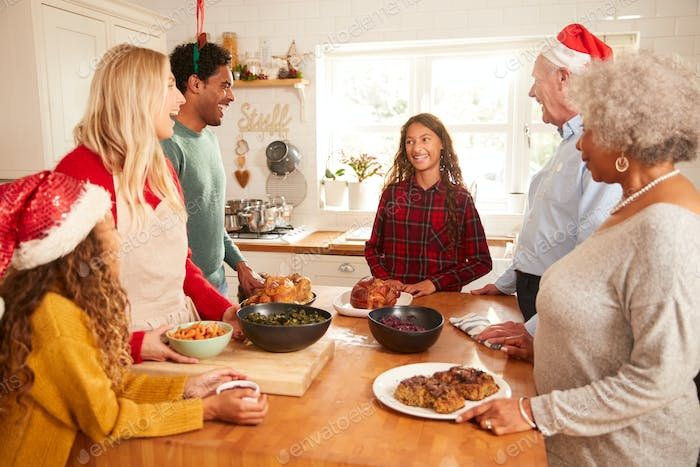 Multi-Generation Family In Kitchen Helping To Prepare Christmas Meal Together