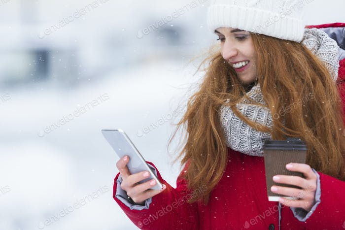 Girl chatting on smartphone and smiling, holding takeaway coffee