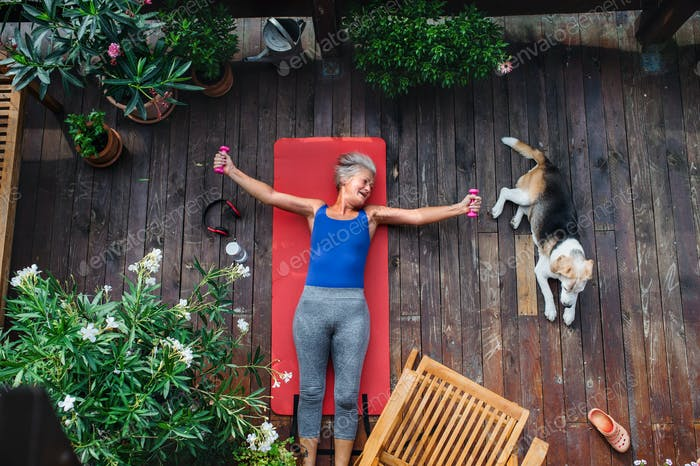 A top view of senior woman outdoors on a terrace in summer, doing exercise.