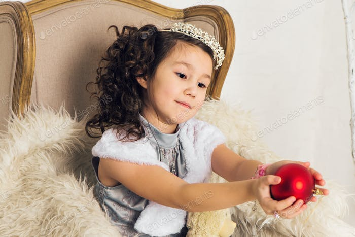 Girl holding christmas red ball to decorate christmas tree