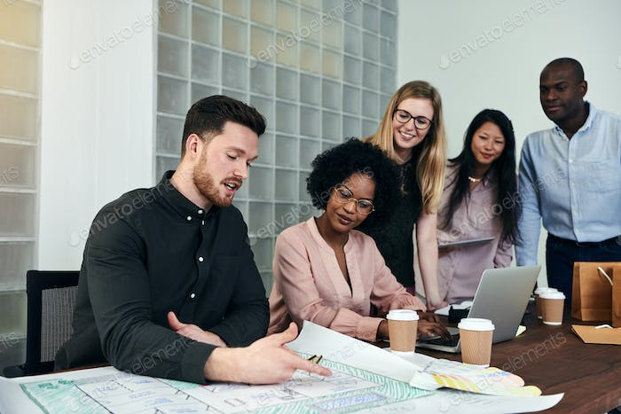 Group of designers discussing blueprints at an office table
