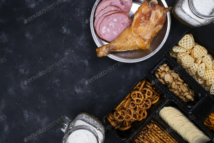 two glasses of beer and snacks, a sausage plate and smoked chicken thighson a concrete black table