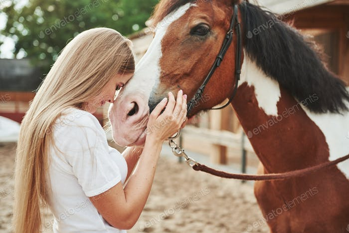 Love animals. Happy woman with her horse on the ranch at daytime