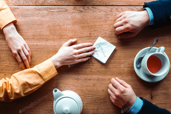 Couple hands with love note on wooden background