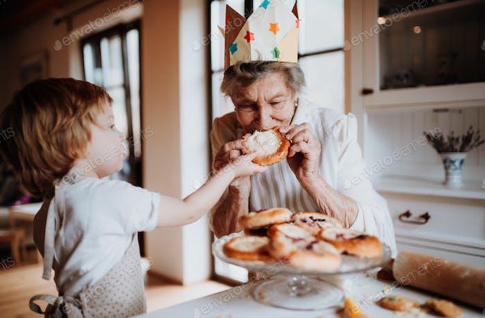 Senior Großmutter mit kleinen Kleinkindjungen machen und essen Kuchen zu Hause.