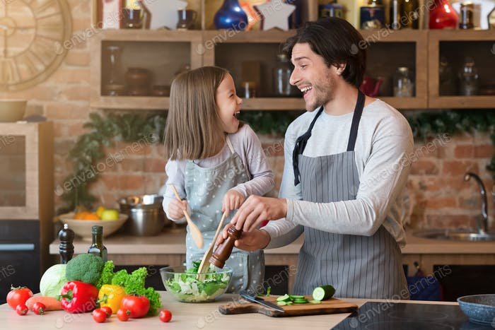 Happy father and little daughter cooking vegetable salad in kitchen