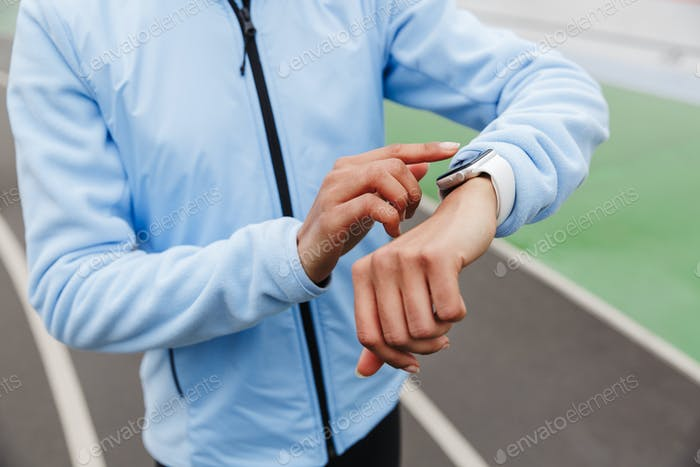 Close up of an african sportswoman using smartwatch