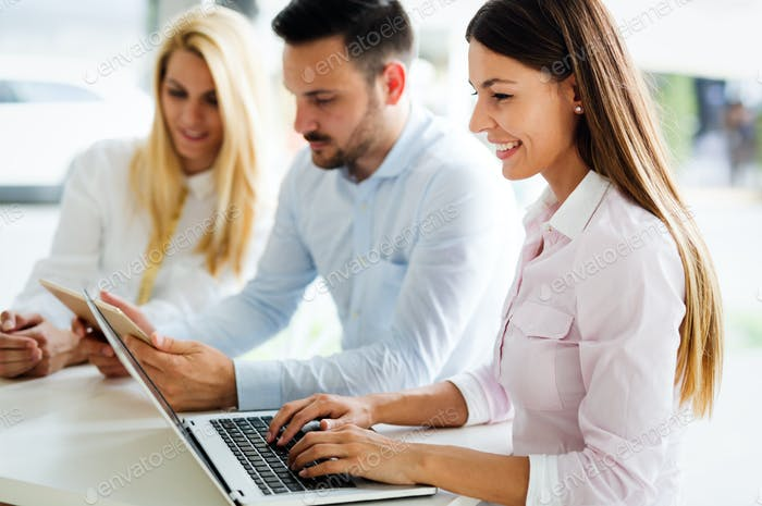 Three young smiling colleagues working together on laptop