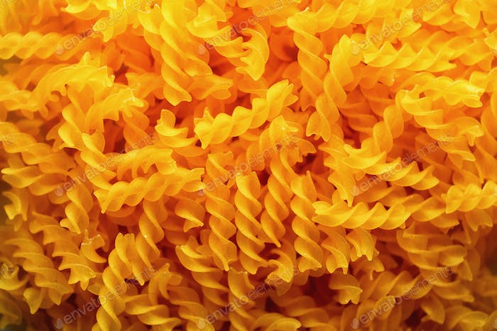Fusilli noodles background, macaroni texture. Uncooked gluten free pasta from blend of corn and rice