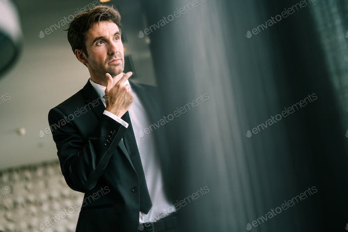 Portrait of a handsome young happy businessman in suit