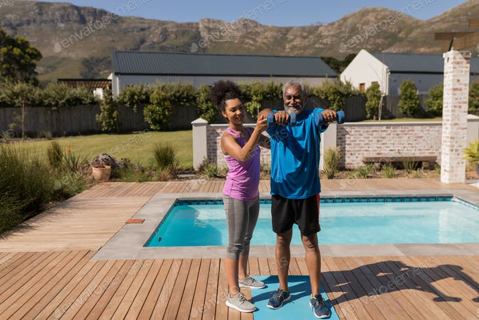 Trainer assisting senior man in performing exercise next to the swimming pool