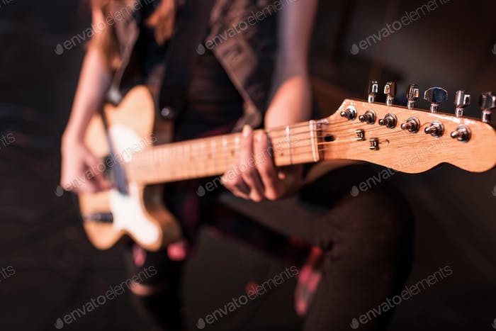 Cropped shot of rock and roll girl playing bass guitar on stage