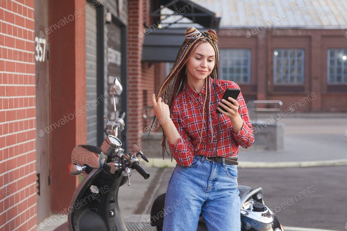 Young woman with colored pigtails using mobile phone on moped