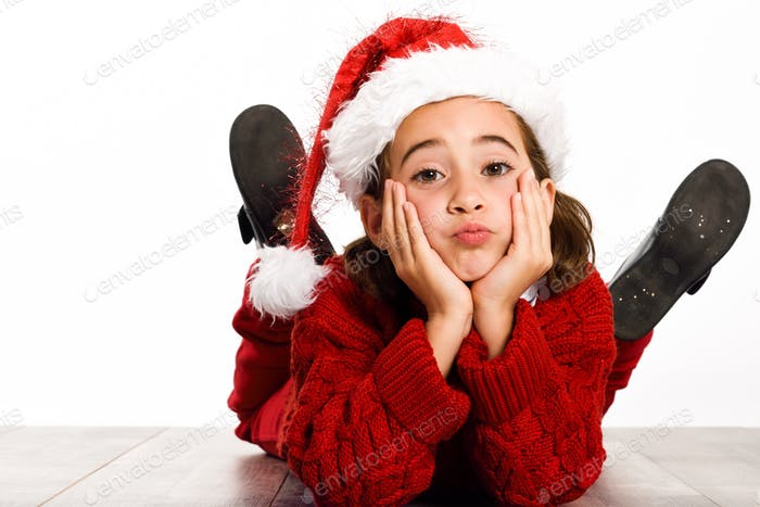 Adorable little girl wearing santa hat laying on wooden floor