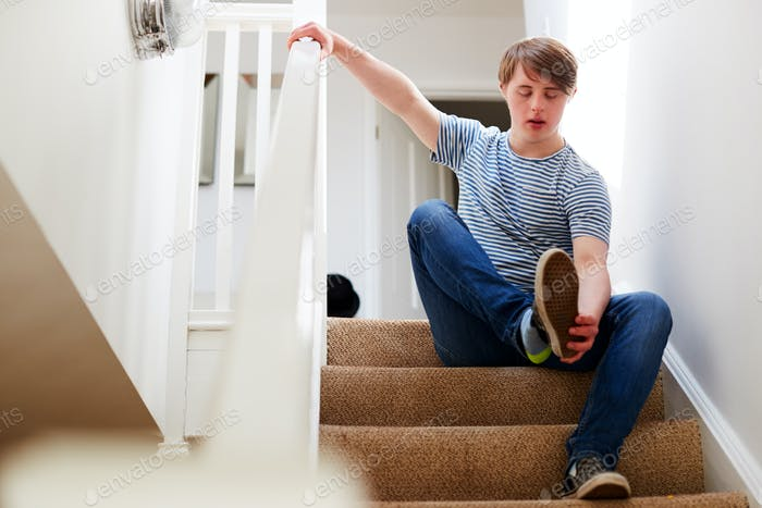 Young Downs Syndrome Man Sitting On Stairs Putting On Shoes At Home