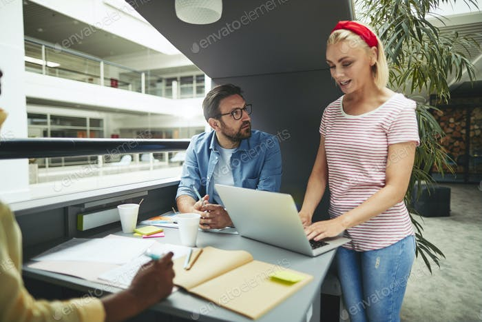 Young businesswoman working with colleagues in a office meeting pod