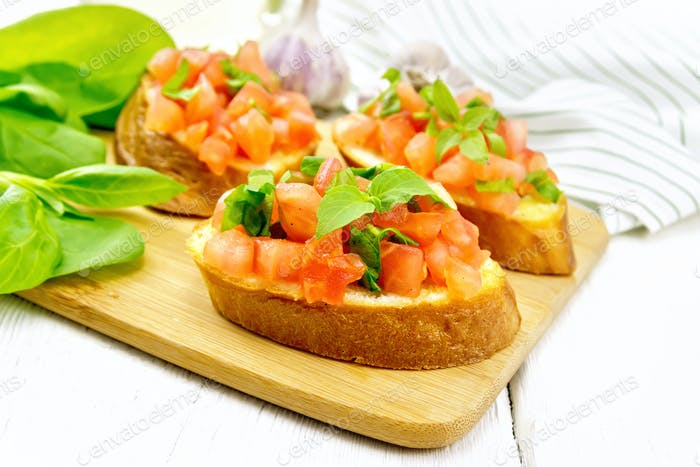 Bruschetta with tomato and spinach on white table