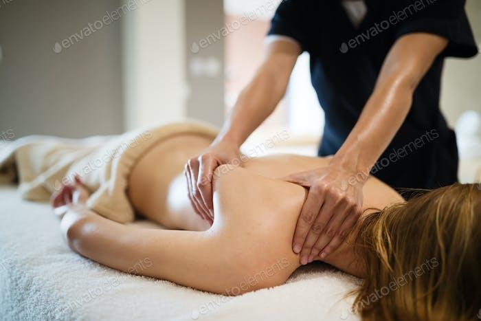 Masseur massaging female client at resort