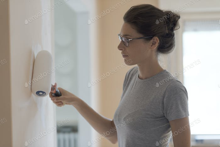 Woman painting walls at home with a paint roller