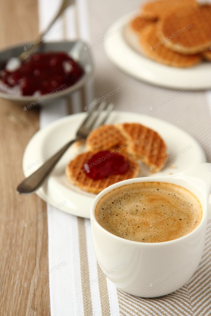 Cup of coffee and mini stroopwafels (syrupwaffles) with jam