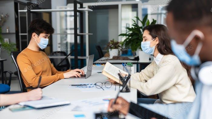 Internationale Menschen mit medizinischen Masken sitzen bei Coworking