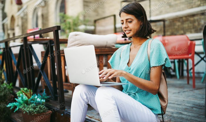 Beautiful woman with laptop outdoor. People, technology, work, fun, study concept