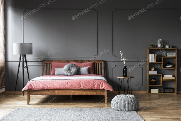 Grey bedroom interior with bookshelf