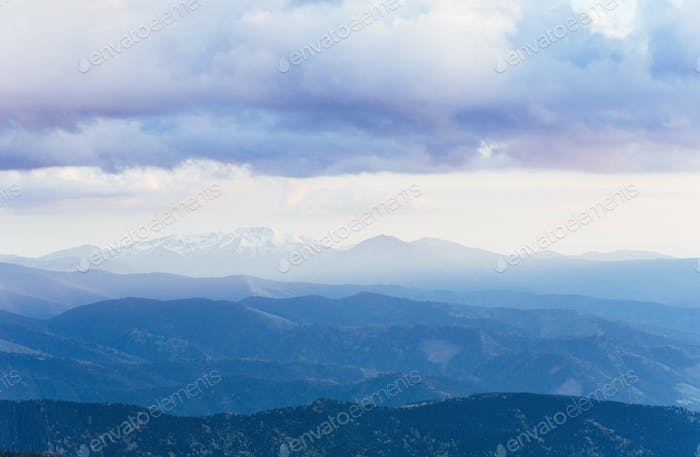 Snowy mountains peaks with mist at sunny day. Carpathian, Ukrain