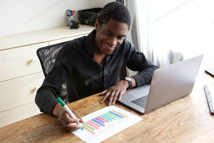 junger Geschäftsmann Zeichnung Diagramm auf Papier