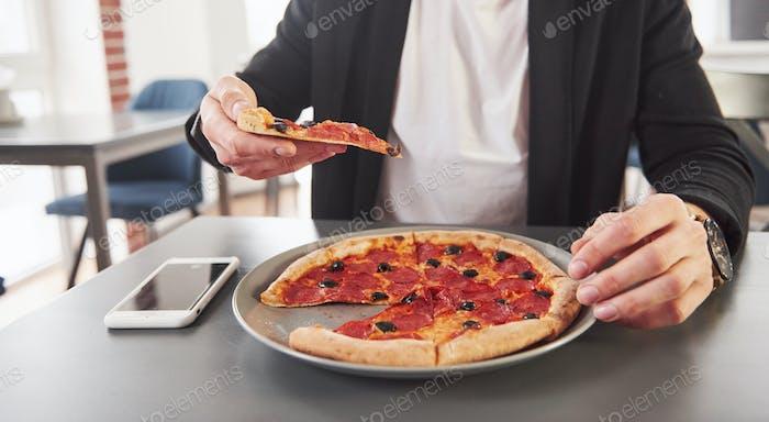Hält eine Scheibe von Lebensmitteln. Bild von vorbereiteter leckerer Pizza mit Wurstringen und Oliven