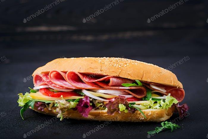 Big sandwich with ham, salami, tomato, cucumber and herbs