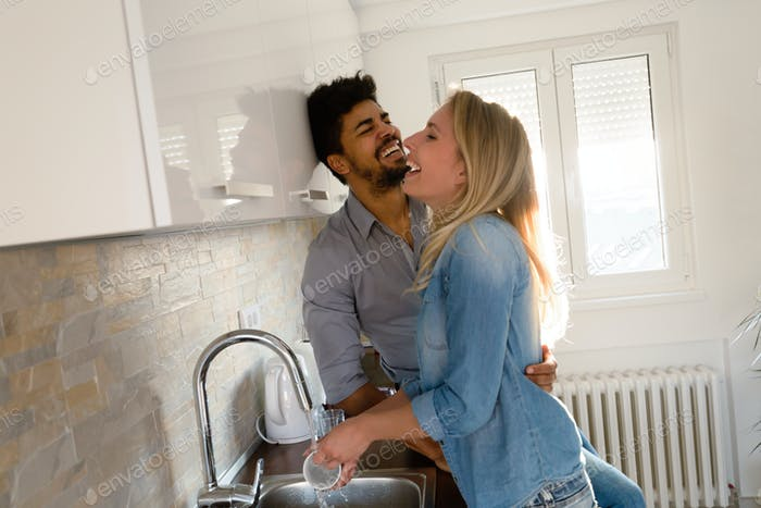 Young couple doing dishes in the kitchen and smiling