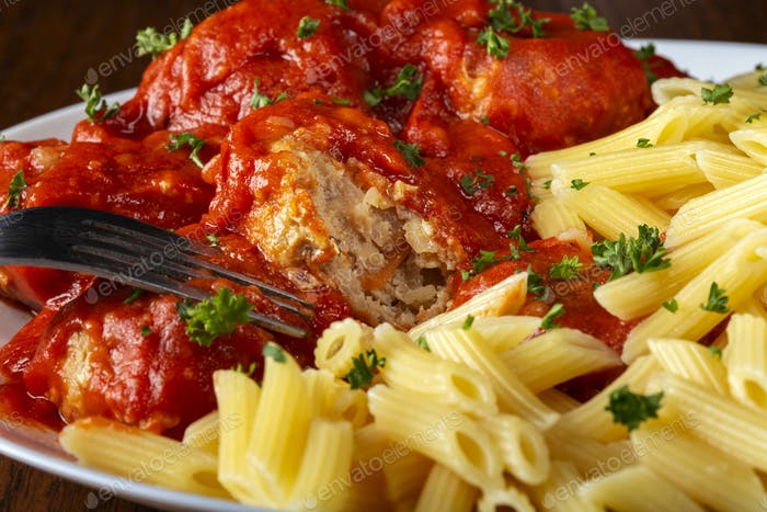 Eating meatballs in tomato sauce with pasta