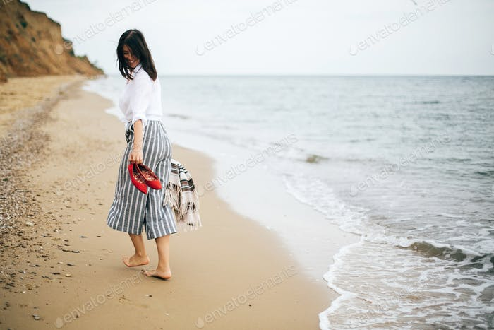 Stylish hipster girl relaxing on beach