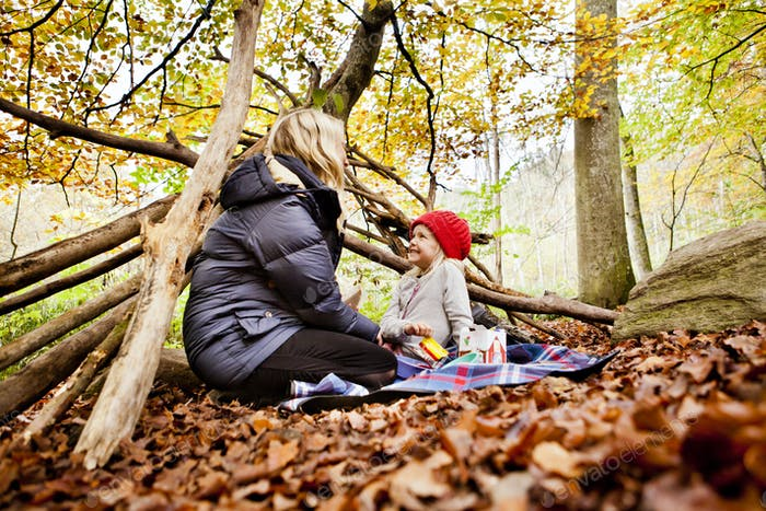 Happy girl looking at mother while enjoying picnic in forest