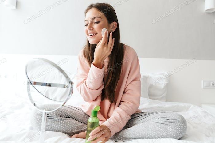 Smiling lovely girl wearing pajamas applying tonic