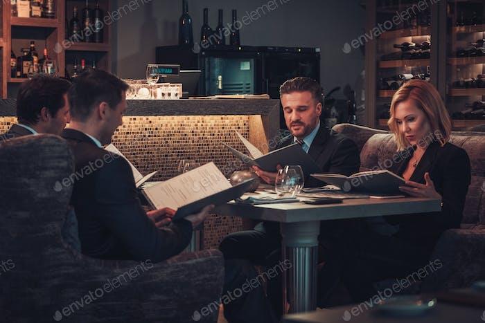 Friends rading menu in a restaurant.