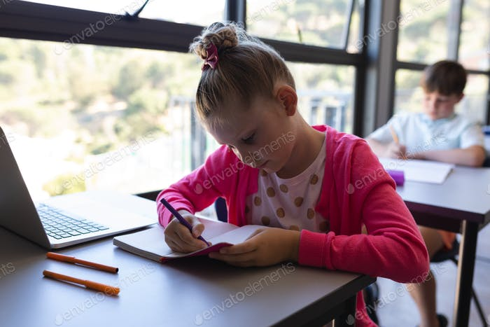Front view of schoolgirl writing on notebook at desk in classroom of elementary school