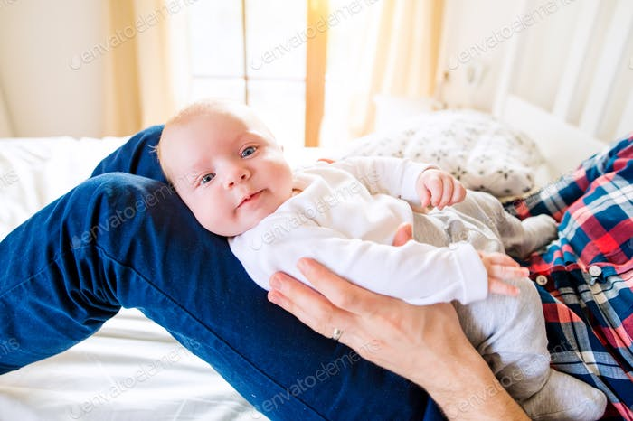 Baby boy held by his father sitting on bed
