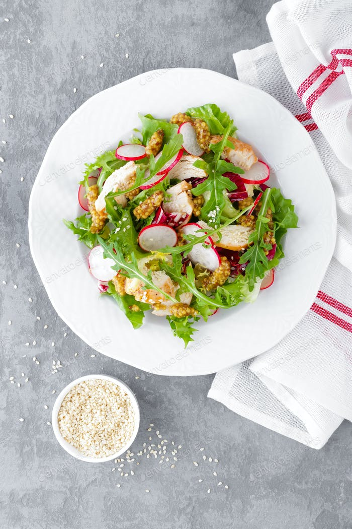 Light spring vegetable salad with radish, lettuce, arugula and chicken meat