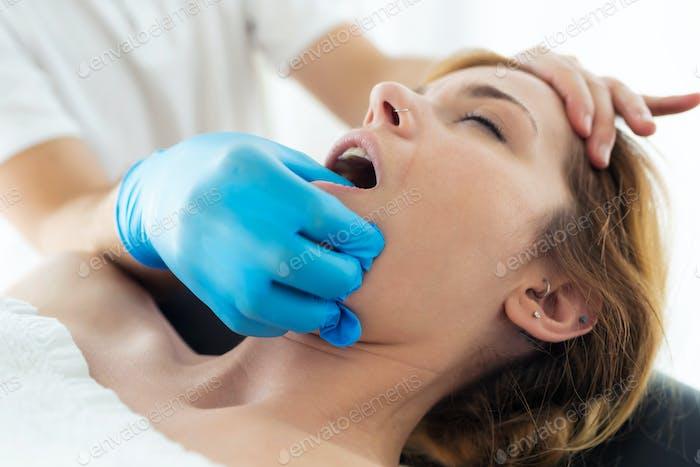 Молодой физиотерапевт делает лечение лица пациенту в физиотерапевтическом кабинете.