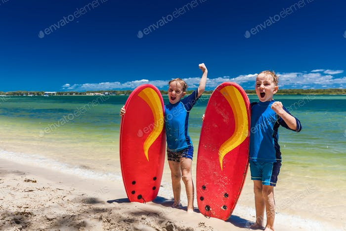 Young surfer brothers have fun on beach learning to surf