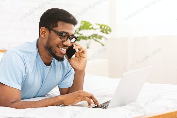 Young millennial man talking by cellphone and using laptop