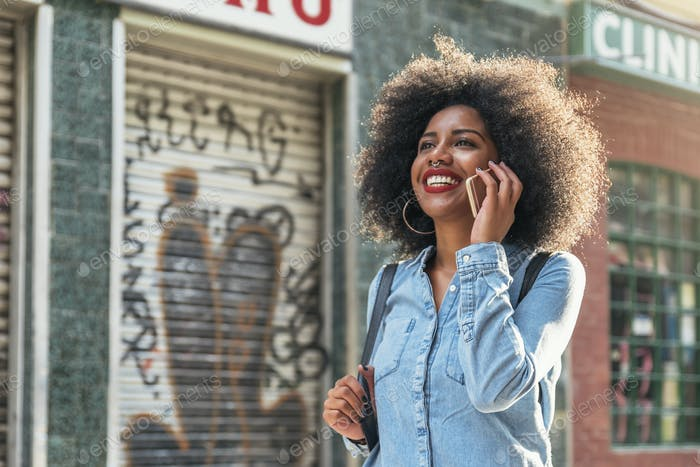 Schöne afro amerikanische Frau mit Handy auf der Straße.