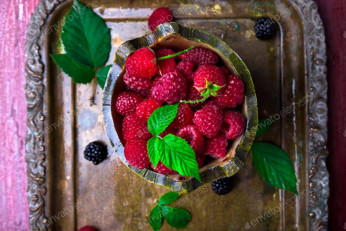 Red raspberry with leaf in a basket on vintage metal tray. Top view.