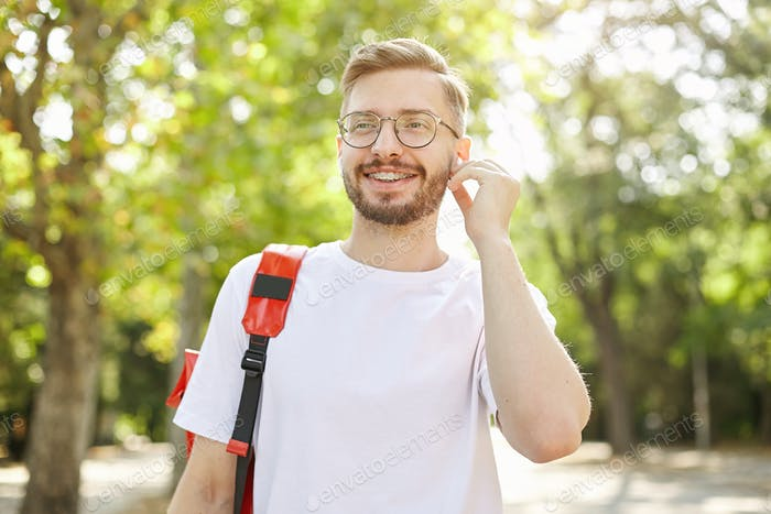 Good looking bearded guy walking through park and going to listen to music with headphones