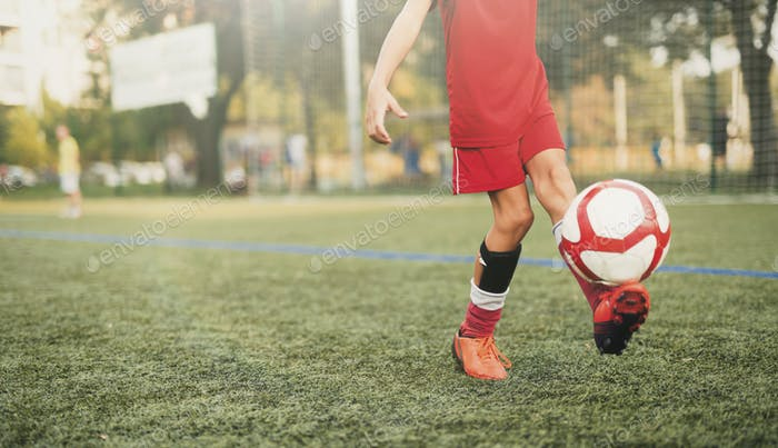 Youngster playing with soccer ball on field