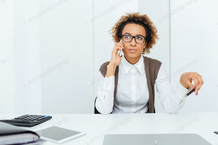 Beautiful african woman accountant sitting and talking on mobile phone