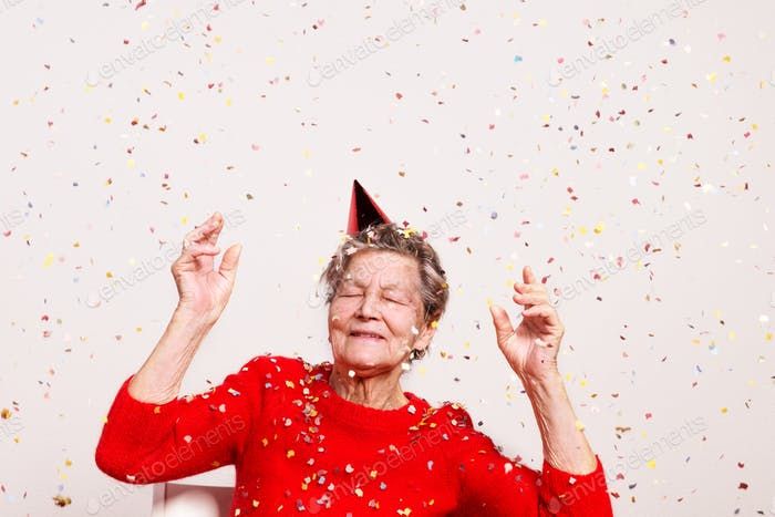 Portrait of a senior woman in studio on a gray background. Party concept.
