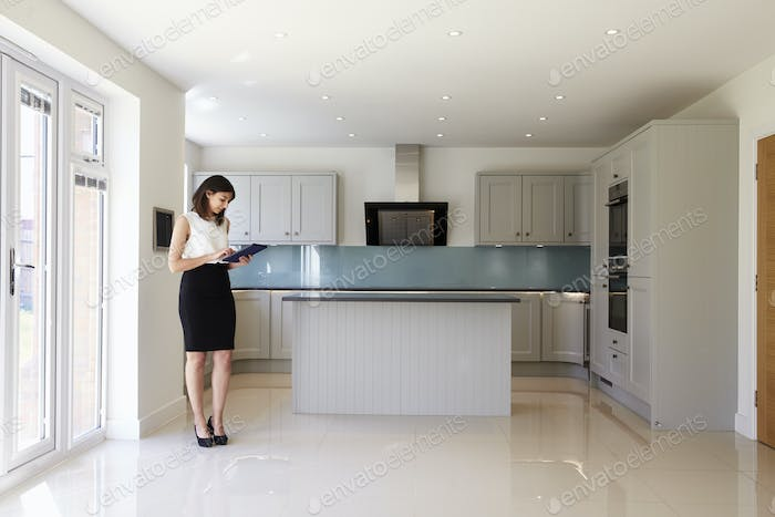 Female Realtor In Kitchen Carrying Out Valuation